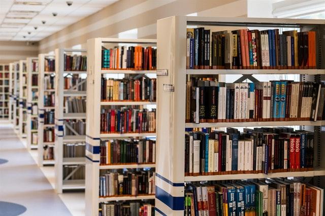 many white library shelves full of books