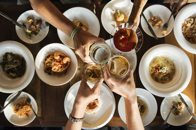 peeple cheers with drinks with food below on a wooden table