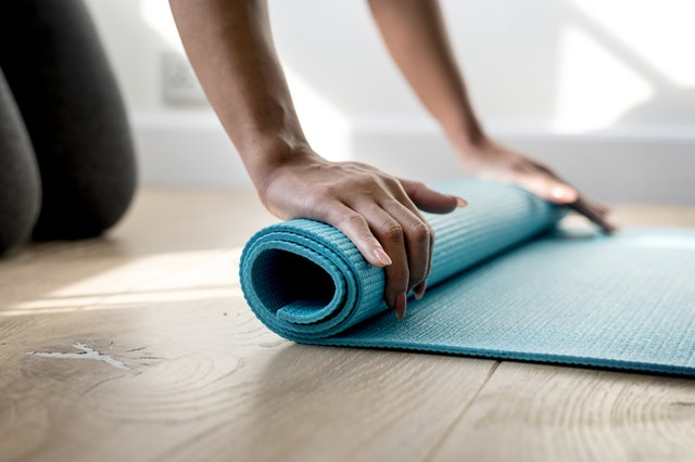 person with blue yoga mat